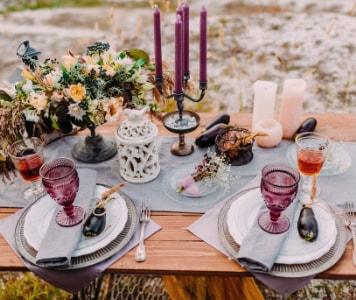 Bunt gedeckter Esstisch mit Blumen und Kerzen
