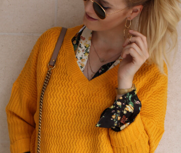 Influencer TheBlondeLion im gelben Pullover und Blümchenkleid