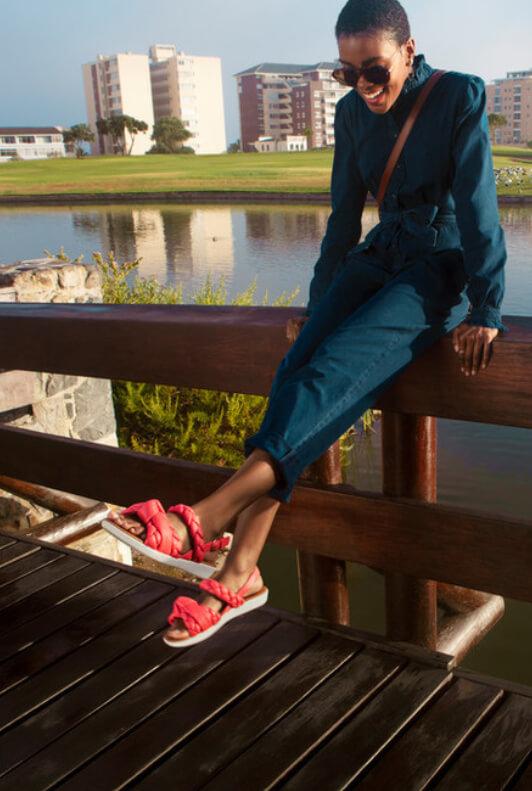 Frau in Jumpsuit mit Sandalen mit geflochtenen Riemen