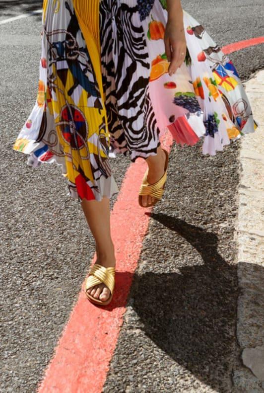 Rock mit buntem Muster und goldene Sandalen