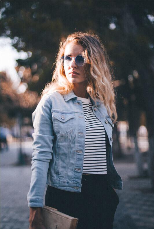 Junge Frau mit kurzer Jeansjacke und Sonnenbrille