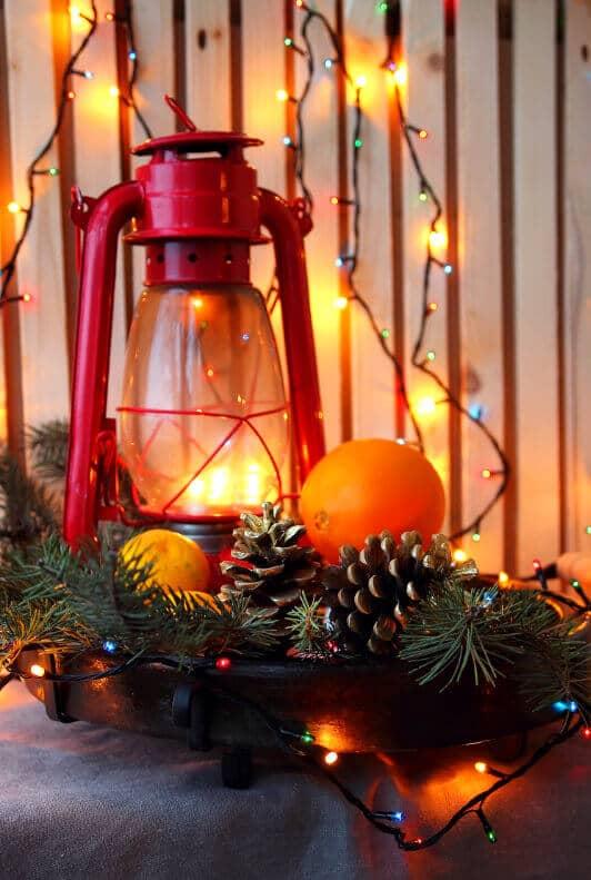 Weihnachtsdekoration mit Sturmlampe, Tannenzapfen und Lichterkette