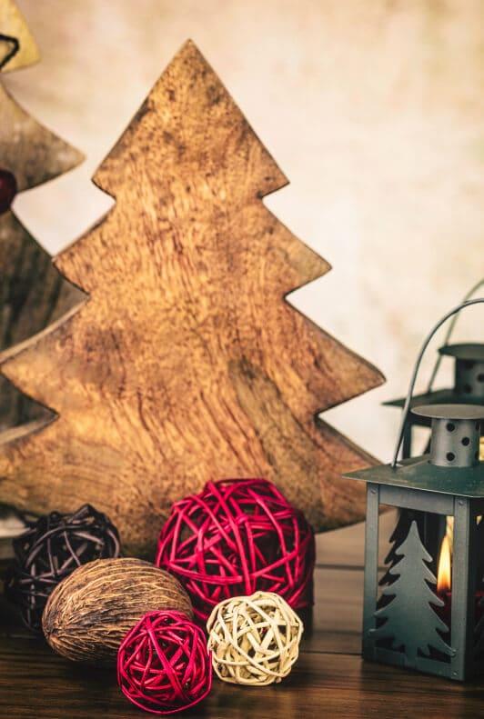 Holzbaum und Weihnachtsdekoration mit Laterne und Rattankugeln