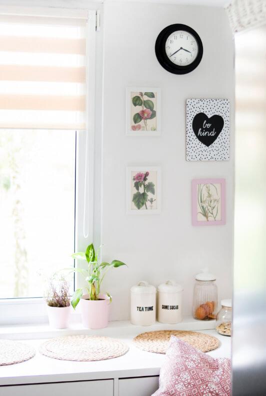 Küche mit Wandbildern, Uhr, Vorratsdosen und Platzdeckchen