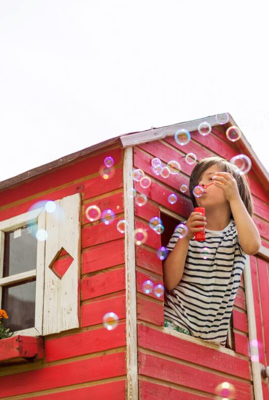 Rotes Spielhaus im Garten und Kind mit Seifenblasen