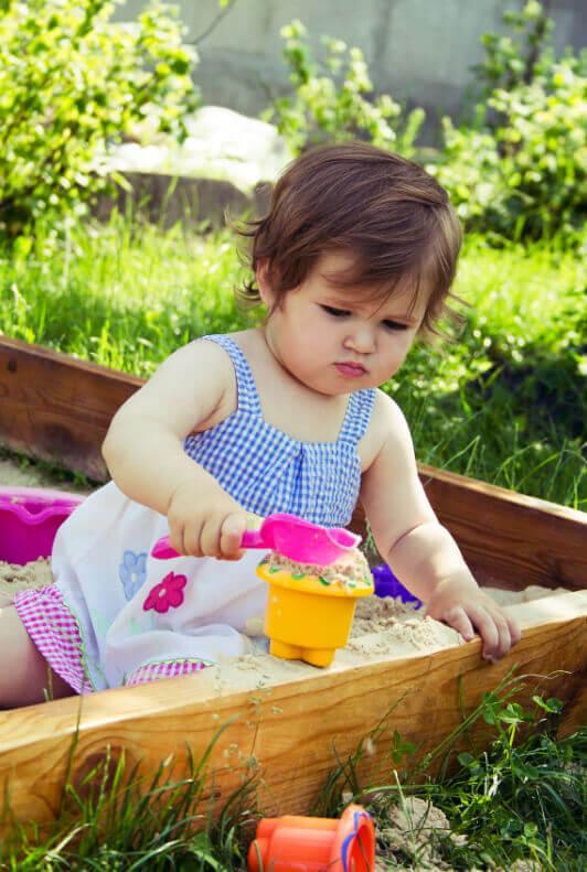 Kind im Sandkasten mit Sandspielzeug