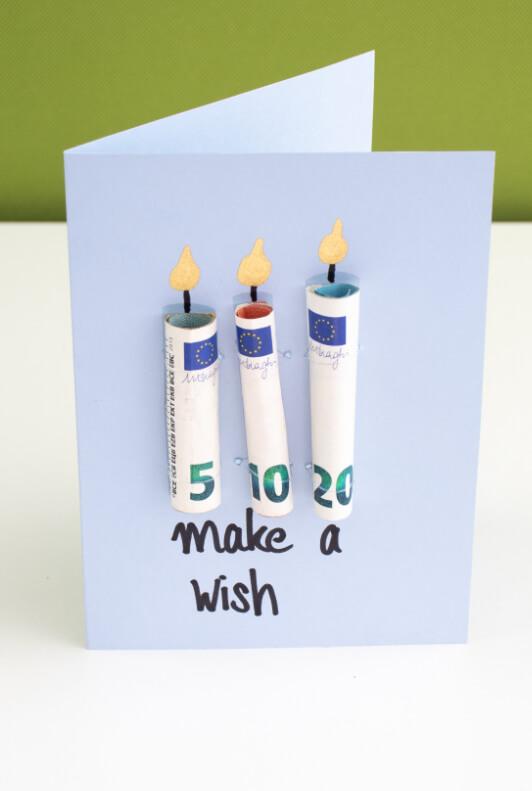 Geschenkkarte mit zu Kerzen gerollten Geldscheinen