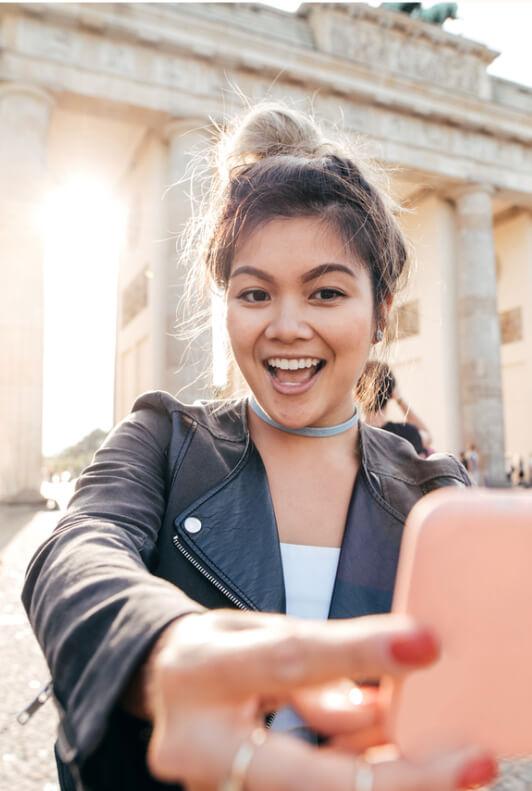 Junge asiatische Frau in Lederjacke macht ein Selfie mit ihrem Smartphoneback