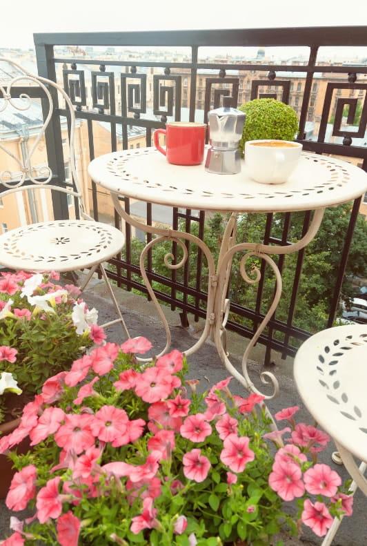Kleiner Balkon mit Bistro-Set Blumen und Kaffeetassen