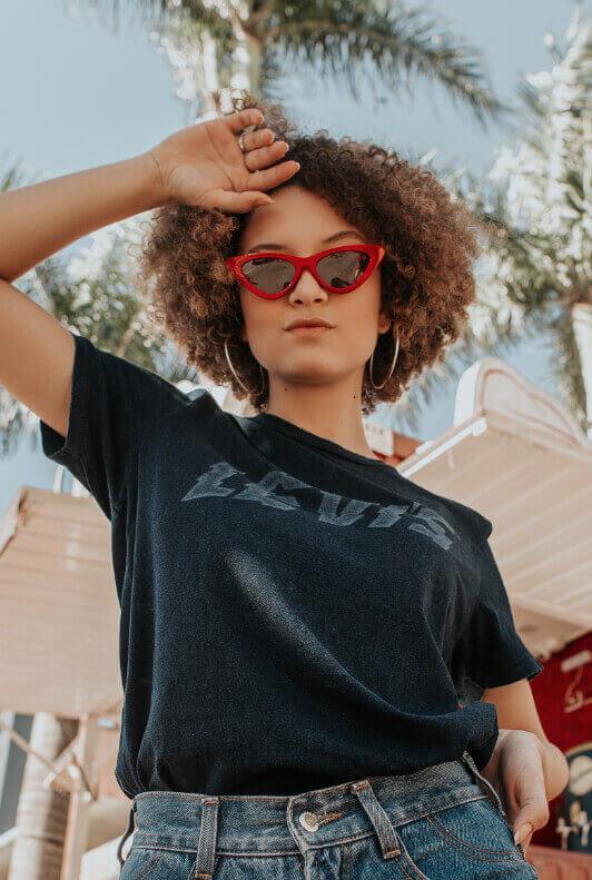 Street Style: Junge Frau mit Afro, Bandshirt und roter Sonnenbrille steht unter Palmen