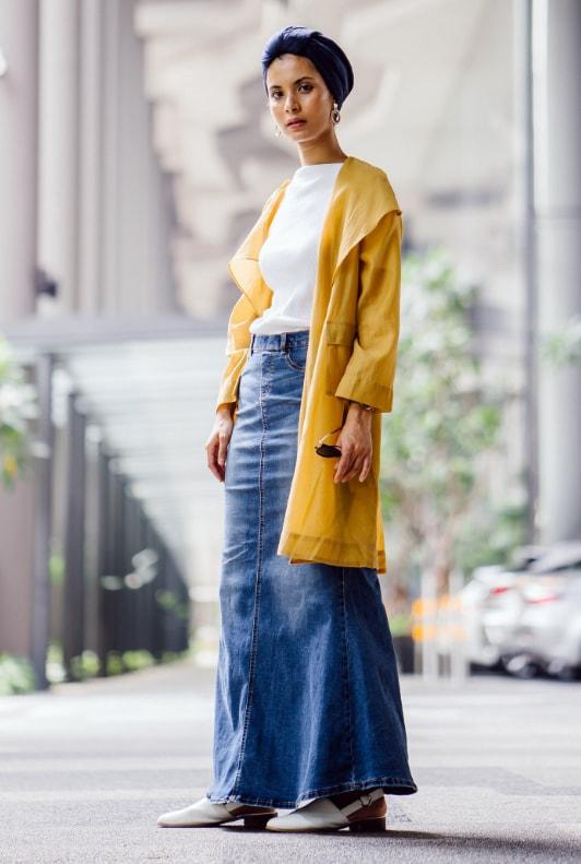 Modest Fashion: Junge Frau mit langem Jeansrock, gelbem Mantel und Turban