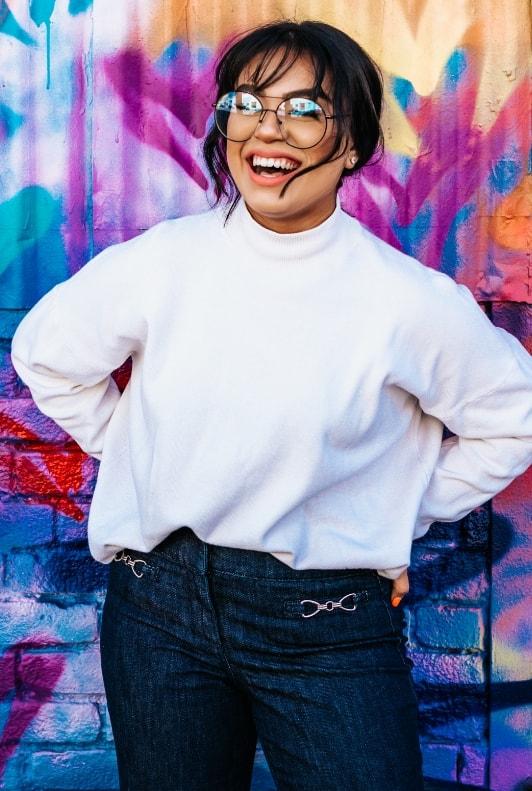 Lachende junge Frau mit Brille und Oversize-Sweatshirt