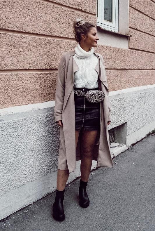 Influencerin trägt schwarzen Lederrock, Trenchcoat und Bauchtasche mit Schlangenmuster