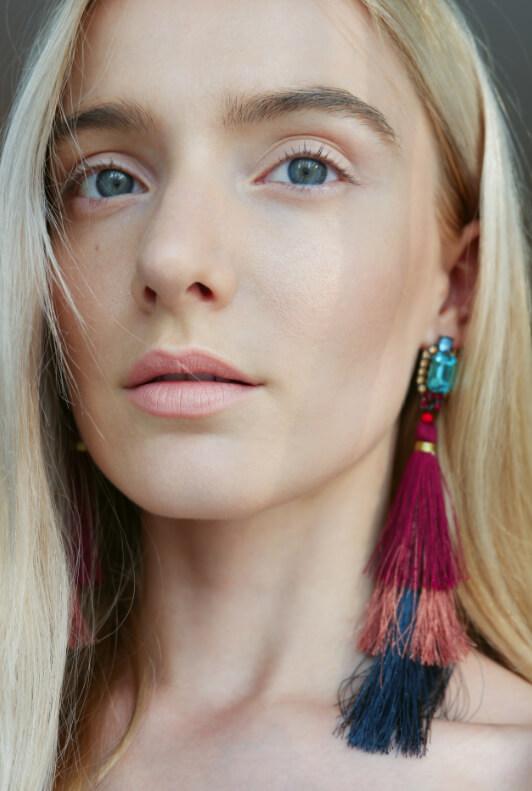 Blonde Frau mit bunten Quastenohrringen