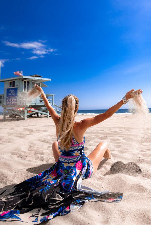Frau am Strand in bunter Tunika
