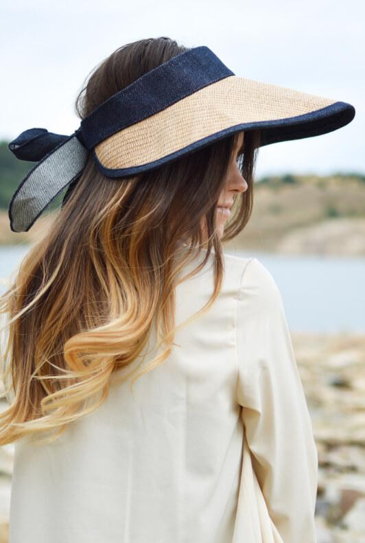 Blonde Frau mit langen Haaren und Visor aus Bast