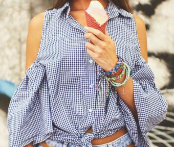 Frau in Jeans-Shorts und Carmenbluse posiert mit Eistüte