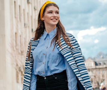 Street Style: Brünette Frau in hellblauer Bluse und schwarzer High-Waist-Jeans