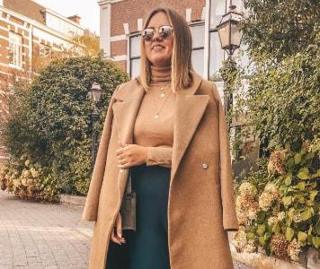 Frau im beigen Mantel, beigen Pullover und grüner Culotte