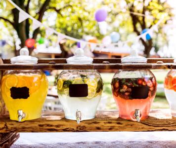 Bunte Wimpelkette, Lampions und Getränkespender auf Gartenparty