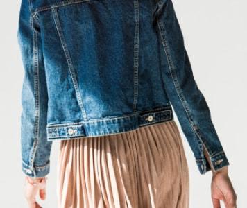 Rückenansicht von Frau in Jeansjacke und rosa Plisseerock