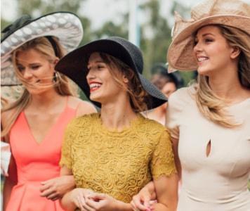 Englische Frauen auf Gesellschaftsevent mit Kleidern, Hüten und Fascinator