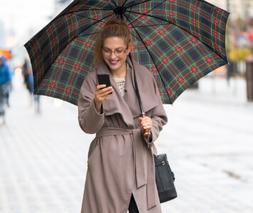Street Style: Frau mit rosa Trenchcoat und kariertem Regenschirm