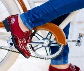 fahrradfahrende Frau in roten Lackleder-Brogues