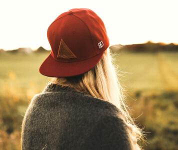 Frau mit roter Basecap auf einer Wiese
