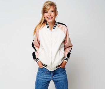 Frau mit Collegejacke und Jeans