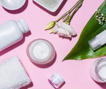 Flatlay Gesichtspflege-Produkte auf pinkem Hintergrund