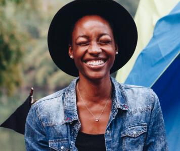 Lächelnde Junge Frau mit Hut sitzt vor einem Zelt