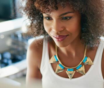 Frau mit Afro sitzt an ihrem Schreibtisch