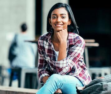Junge Frau mit rot-weiß-kariertem Hemd, Jeans und schwarzen Sneakern