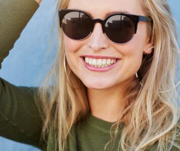 Frau mit Sonnenbrille und grünem Pullover