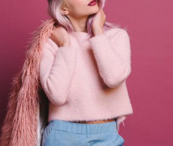 Junge Frau mit rosa Haaren, rosa Pullover und hellblauer Hose steht vor einer pinken Wand
