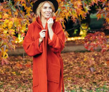 Frau in rotem Mantel in Herbstlandschaft