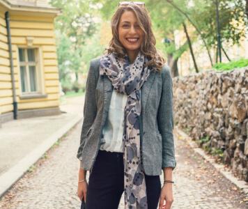 Frau mit grauem Blazer und fliederfarbenem Halstuch