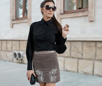 Brünette Frau mit schwarzer Bluse, Taupe Rock und beigefarbenen Stilettos