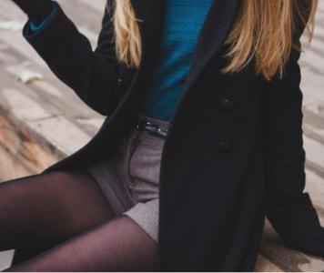 Sitzende junge Frau in Shorts, Strumpfhosen, schwarzem Mantel und blauer Mütze