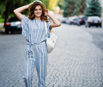 Street Style: Frau in gestreiftem Overall mit Strohhut auf der Straße