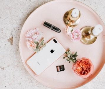 Rosa Tablett mit Kerzen, Blumen, Lippenstift und Smartphone