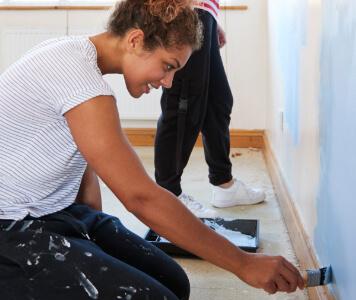 Zwei Frauen streichen eine Wand mit Farbroller und Pinsel