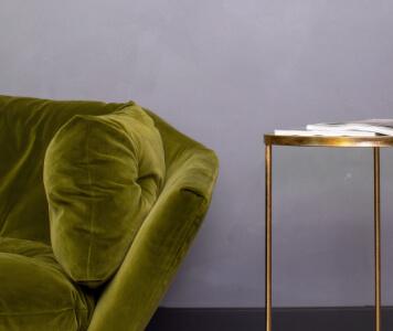 Grünes Sofa und goldener Beistelltisch vor hellgrauer Wand