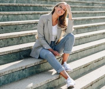 Frau kombiniert weiße Sneaker zu Jeans und schwarzem Sweatshirt