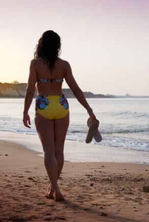 Frau am Strand mit gelbem High Waist Biniki