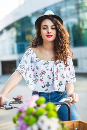 Junge Frau im floralen Rüschentop auf Fahrrad