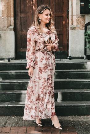Blonde Frau in elegantem Volantkleid mit langen Ärmeln und Pumps in Metallic