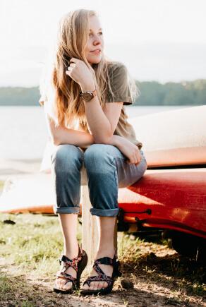 Blonde Frau mit Teva Trekkingsandalen, Jeans und T-Shirt